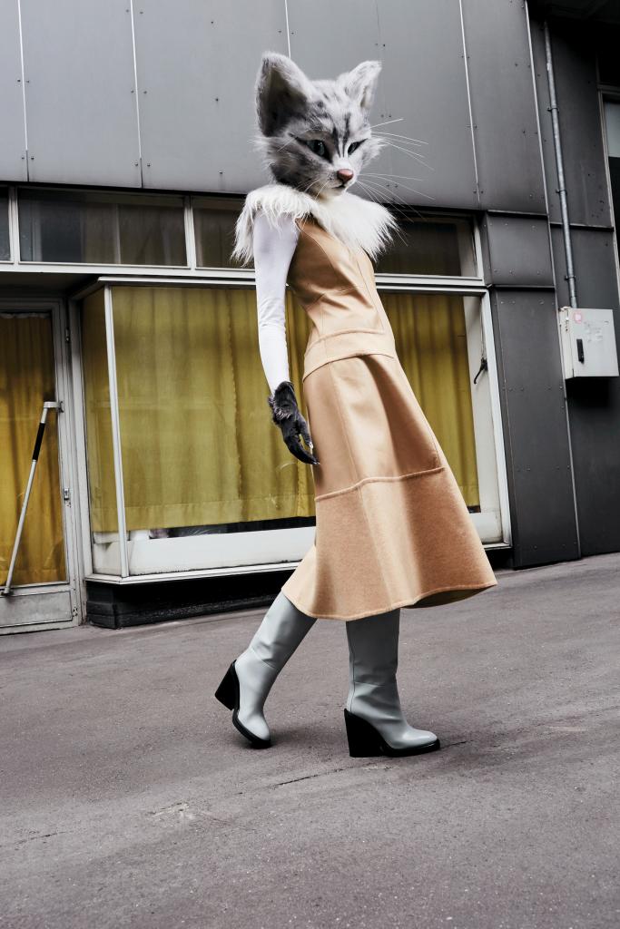 Mode-Bloggerin Pheline von Fou de Pheline trägt ein Outfit im aktuellen femininen Leder Look. Dafür hat sie ein beiges, ausgestelltes Wollkleid mit Lederpatches und weiße Stiefel mit Keilabsatz von Hermès ausgewählt.