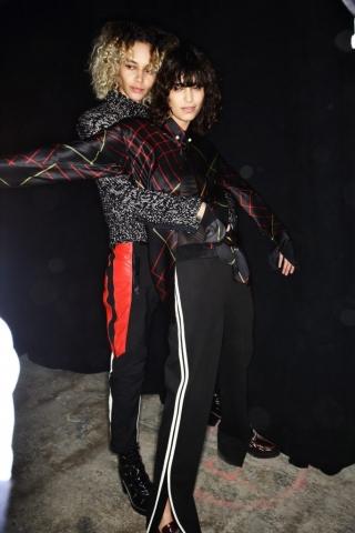 Auf dem Bild sind zwei Models im Backstagebereich bei der H/W-Modenschau 2016 von Rag & Bone zu sehen. Sie tragen je eine Trainingshose. Das linke Model kombiniert dazu einen Strickpullover. Das rechte Mädchen hat eine Bluse an.