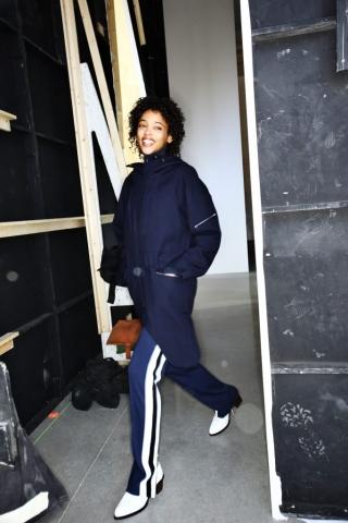 Auf dem Foto ist ein Model im Backstagebereich bei der H/W-Modenschau 2016 von dem Modelabel Lacoste zu sehen. Sie trägt eine blaue Trainingshose, einen blauen Parka und weiße Herrenschnürer.
