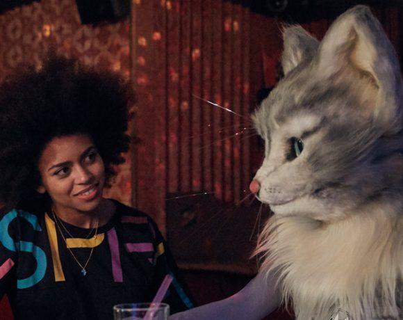 Auf dem Foto sind Aminata Belli und Katzenlady Pheline zu sehen. Die beiden sitzen an einer Bar, sprechen über Musik und eine Playlist und lauschen einem Song.