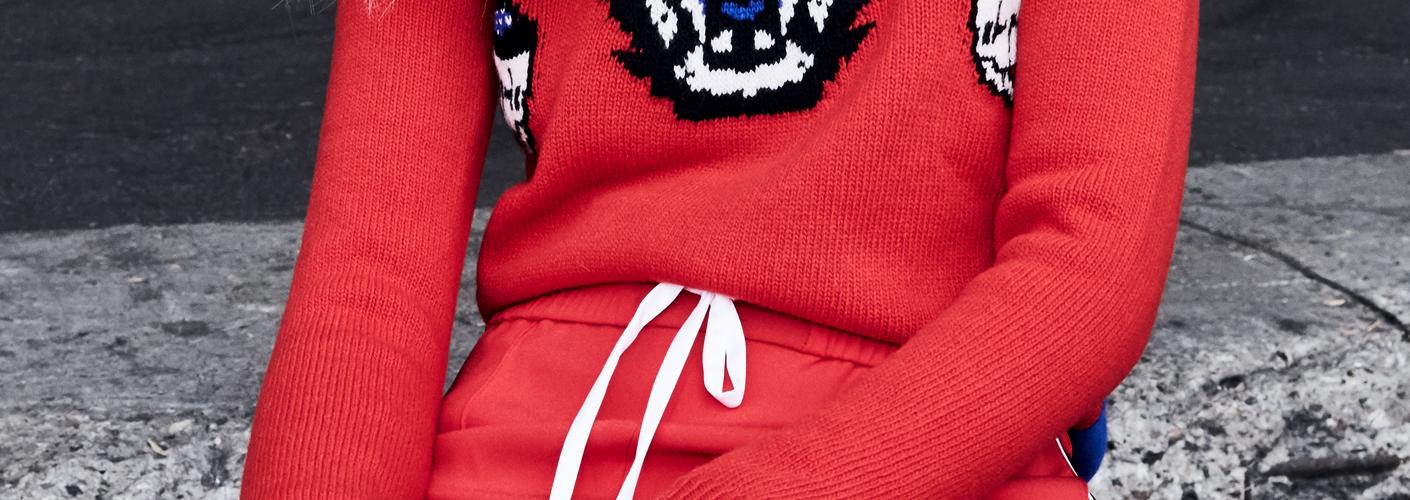 Auf dem Bild ist Katzenlady Pheline im Anschnitt zu sehen. Sie tragt eine rote Trainingshose von Kenzo und einen Roten Strickpulli von Gucci.
