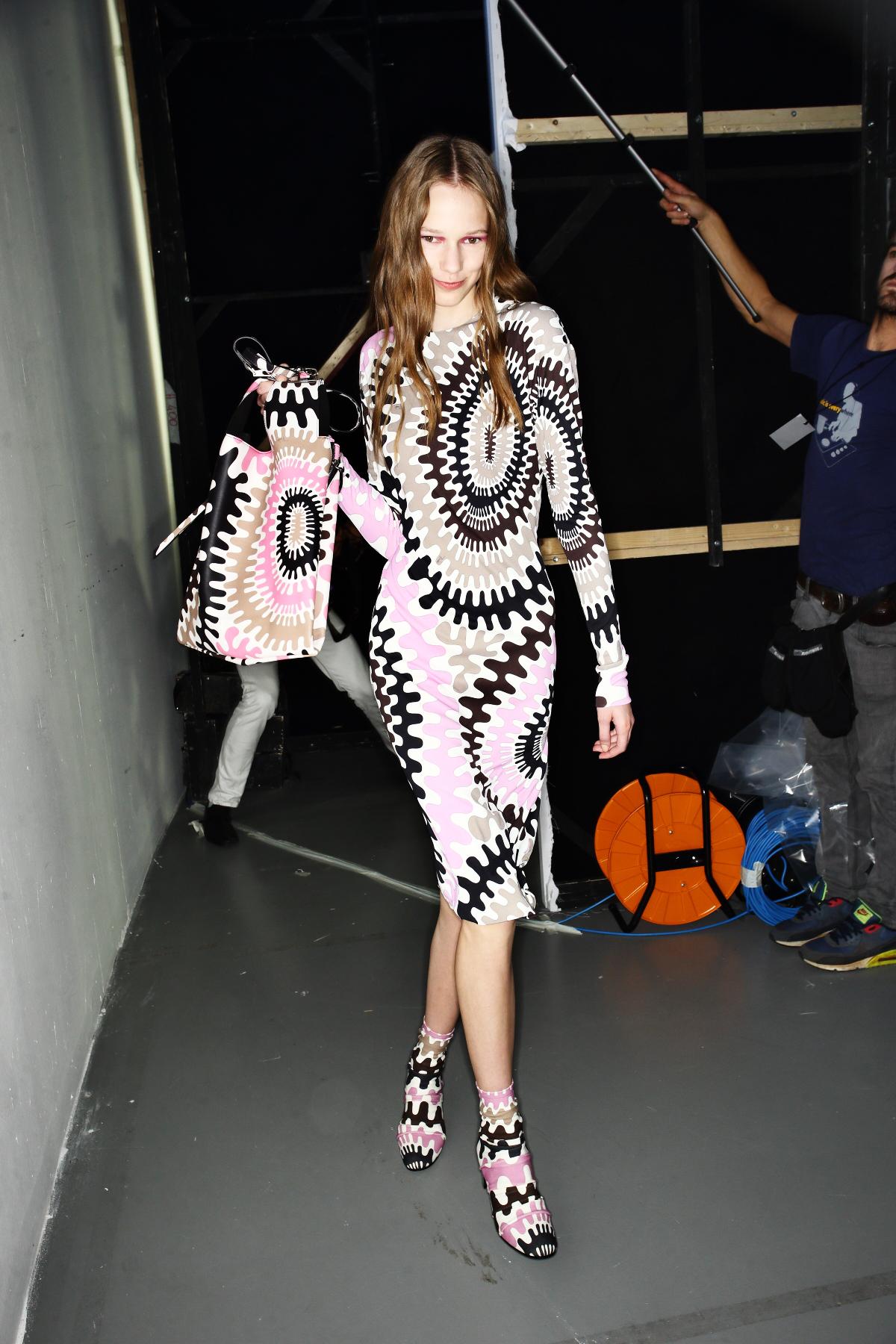 Auf diesem Bild sieht man ein Model im Backstage Bereich der Emilio Pucci Fashionshow mit pinkem Lidschatten, der auch Rouge sein könnte.