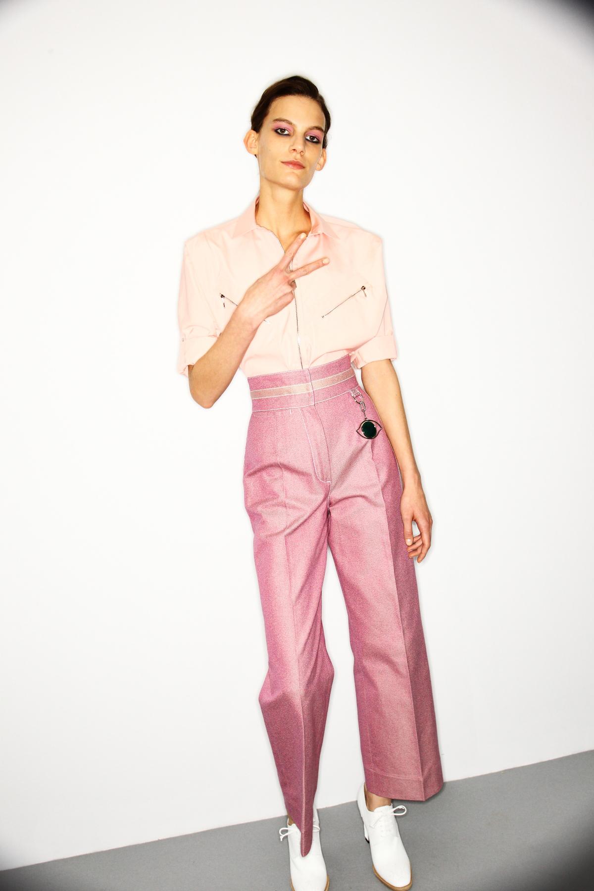 """Hier sieht man ein Mädchen im Backstage Bereich der Hermès Modenschau mit rosa farbenem Lidschatten passend zum Make Up Trend """"Rouge allover""""."""