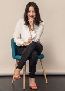 """Auf dem Bild sitzt Ninon Götz, die Gründerin vom online Magazine """"Très Click"""" auf einem türkisfarbenen Stuhl und hat die Beine übereinandergeschlagen. Sie trägt eine cremefarbene Bluse, eine dunkelgraue Jeans, orangefarbene Sandaletten und lächelt in die Kamera. Ninon Götz hat eine Playlist, bestehend aus 12 teilweise melancholischen Songs für foudepheline zusammengestellt."""