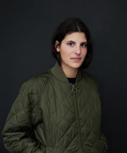 Auf dem Foto ist Aicha Reh zu sehen. Sie ist die Modeleitung beim Neon und Nido Magazin. Sie trägt einen grünen Blouson und für foudepheline.com die Playlist für den Monat August erstellt.