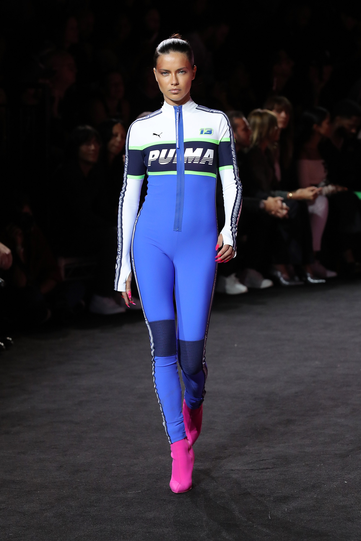 Auf dem Foto ist ein Model zu sehen. Sie befindet sich auf der Fashion Show von FENTY Puma by Rihanna. Sie trägt einen enganliegenden blau-weißen Rennanzug mit Zipper und mit Puma Schriftzug über der Brust. Sie kombiniert dazu spitze, pinke Booties.