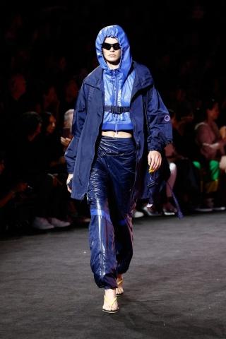Auf dem Foto ist ein Model zu sehen. Sie befindet sich auf der Fashion Show von FENTY Puma by Rihanna. Sie trägt einen hellblauen cropped Hoodie, eine dunkelblau glänzende Jogginghose und eine dunkelblaue Outdoor-Jacke, die vor der Brust durch einen Gurtverschluss zusammengehalten wird..
