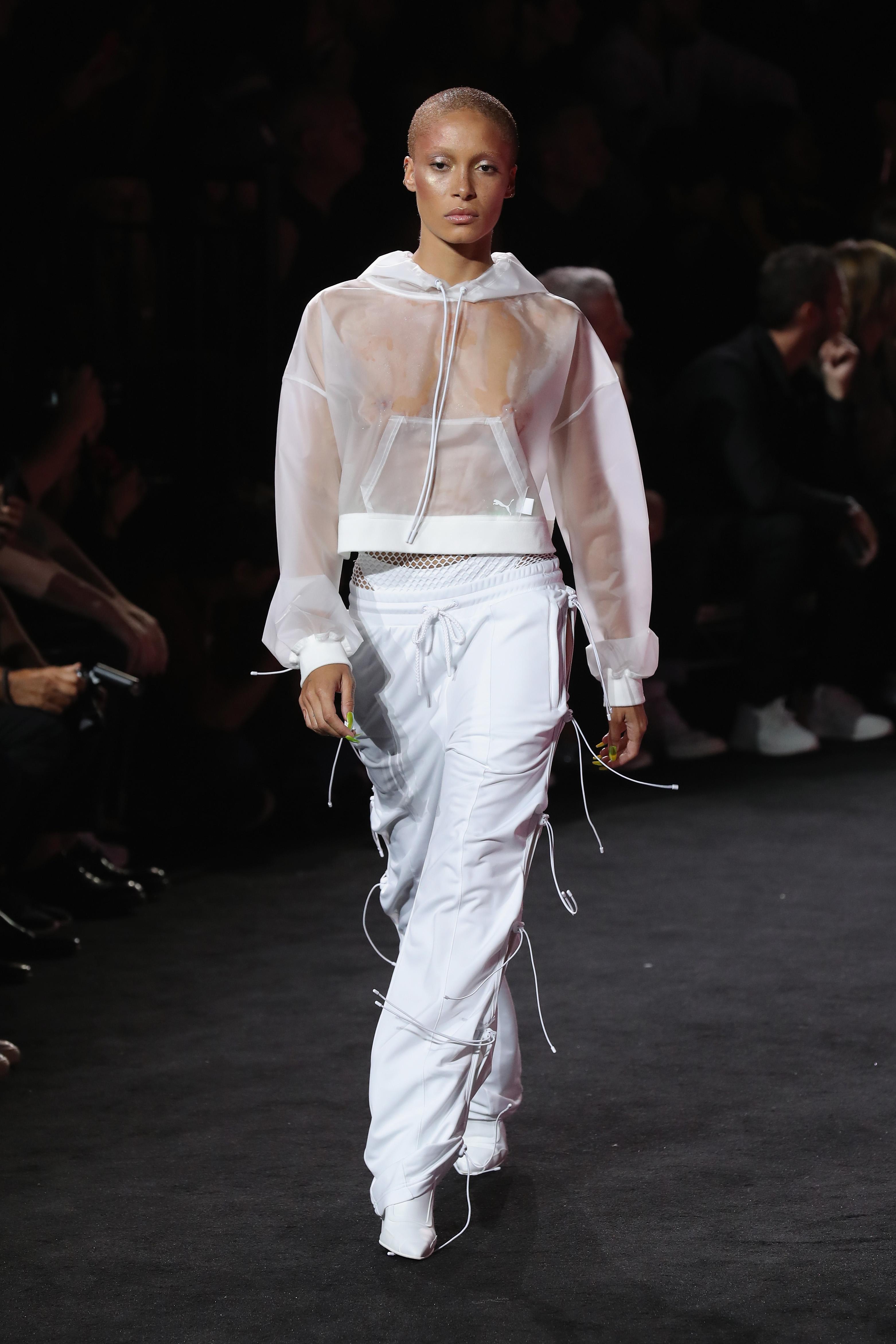 Auf dem Foto ist das Model Adwoa Aboah zu sehen. Sie befindet sich auf der Fashion Show von FENTY Puma by Rihanna. Sie trägt einen trasparenten weißen Hoodie, eine weiße Jogginghose mit seitlicher Schnürung und spitze, weiße Booties.