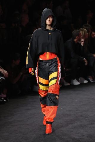 Auf dem Foto ist ein Model zu sehen. Sie befindet sich auf der Fashion Show von FENTY Puma by Rihanna. Sie trägt einen schwarzen cropped Hoodie, eine Jogginghose im Racing Style. Unter dem Hoodie blitzt ein roter Badeanzug mit orangefarbenem Zipper hervor. Zu dem Look kombiniert sie spitze, rote Booties.
