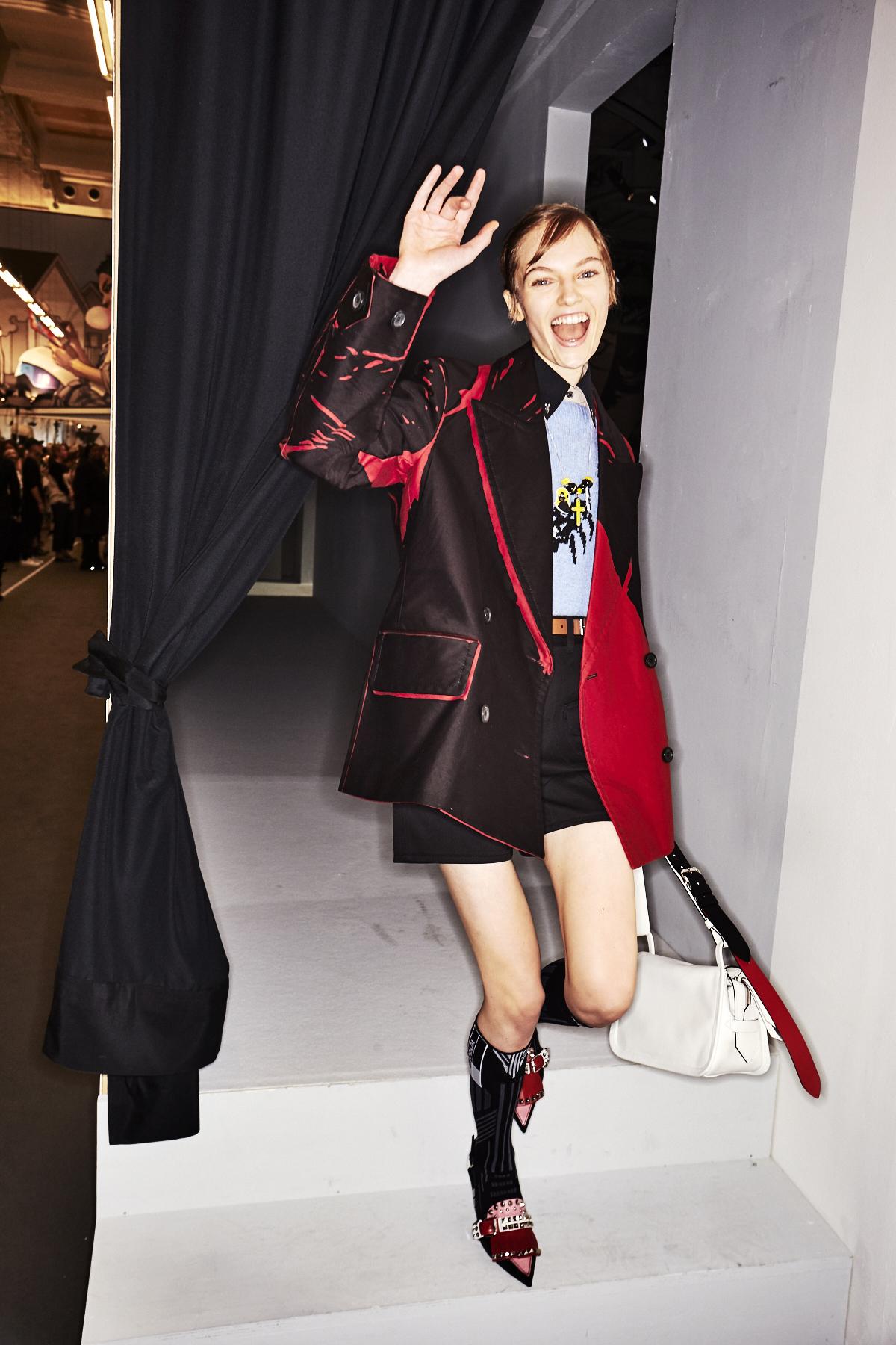 Ein Model im Backstage Bereich der Prada F/S 2018 Show trägt ein oversized Sakko und Shorts.
