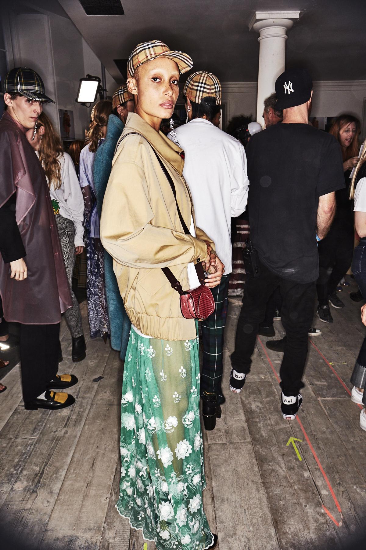 """Auf dem Foto ist ein  Model im Backstagebereich der Modenschau vom Briten Christopher Bailey für Burberry zu sehen. Das Mädchen ist Adwoa Aboah, die Gründerin der Plattform """"GURL`S Talk"""". Auf dem Kopf trägt sie eine karierte Baseball Cap im klassischen Buberrycheck-Muster. Das Model trägt einen beigefarbenen Blouson und bodenlanges Kleid aus grüner Spitze, die mit weißen Blüten bestickt ist. Außerdem trägt Adwoa eine rote Micro-Bag und einen Statement-Ohrring."""