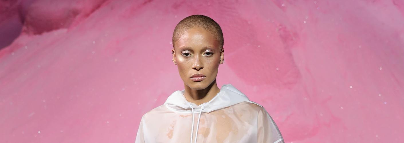 Auf dem Foto ist das Model Adwoa Aboah zu sehen. Sie befindet sich auf der Fashion Show von FENTY Puma by Rihanna. Sie trägt einen trasparenten weißen Hoodie.