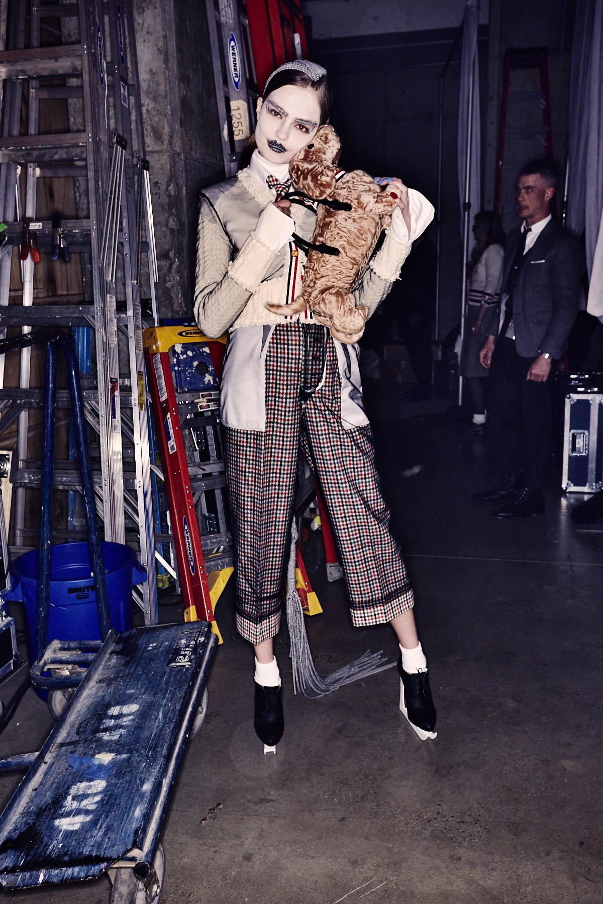 Ein Model im Backstage Bereich der Thom Browne Herbst/Winter 2017 Show trägt ein Outfit mit Karohose und Hemd mit weißem Kragen.