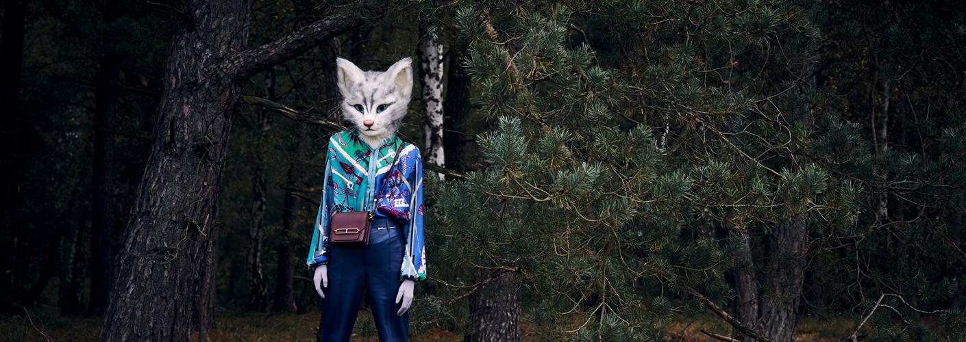 Auf dem Foto ist Katzenlady Pheline zu sehen. Sie steht in einem Wald und trägt eine Seidenbluse mit Scarfprint, eine blaue Lederhose und eine weinrote Umhängetasche. Der Look ist aus der Herbst/Winter Kollektion von Hermès.