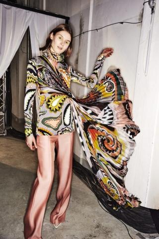 Auf dem Foto ist ein Model im Backstagebereich der H/W Modenschau von Emilio Pucci zu sehen. Sie trägt ein buntes Seidenoberteil mit einem Scarfprint Muster. Das Foto stammt von Sonny Vandevelde.