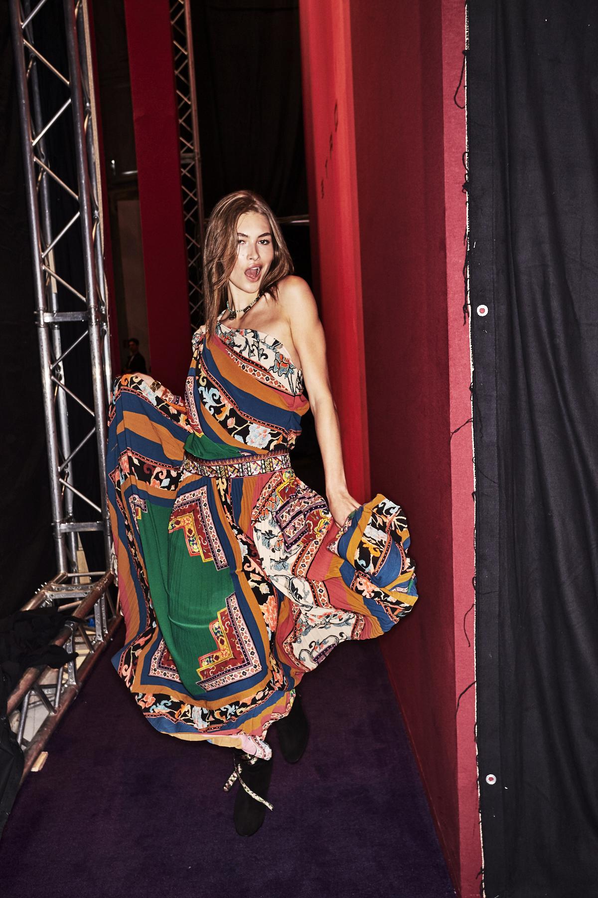 Auf dem Foto ist ein Model im Backstagebereich der H/W Modenschau von Etro zu sehen. Sie trägt ein buntes Seidenkleid mit einem Scarfprint Muster. Das Foto stammt von Sonny Vandevelde.