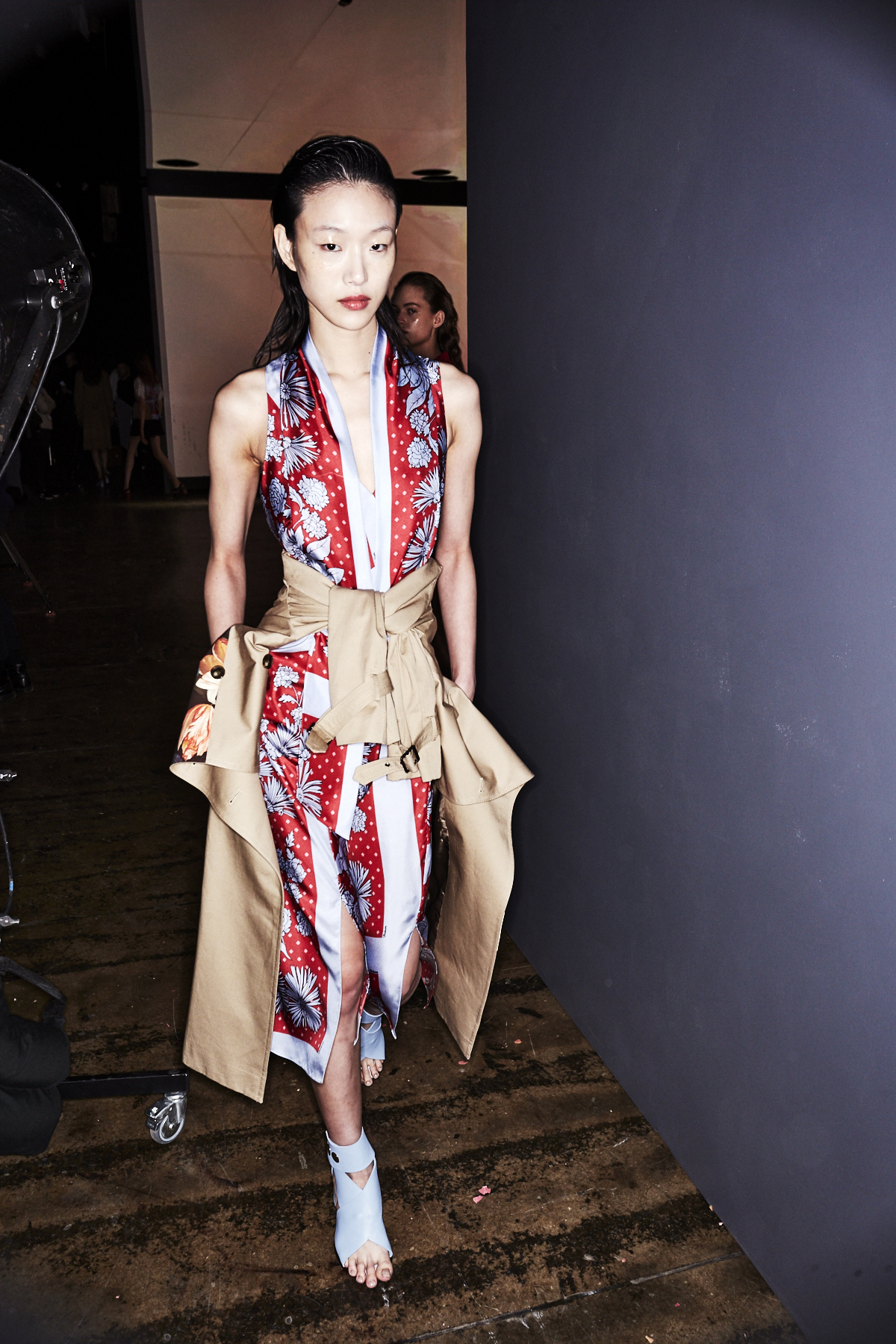 Auf dem Foto ist ein Model im Backstagebereich der H/W Modenschau von Designer Thakoon zu sehen. Sie trägt ein hellblau-rotes Seidenkleid mit einem Scarfprint Muster. Um ihre Taille hat sie einen Trenchcoat gebunden. Das Foto stammt von Sonny Vandevelde.