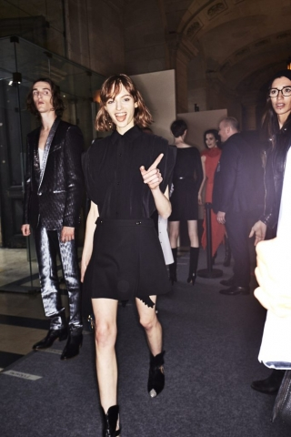 Auf dem Foto ist ein Model im Backstage-Bereich der ersten Modenschau von Designerin Claire Waight Keller für das Modehaus Givenchy in Paris zu sehen. Es handelt sich um die Präsentation der F/S 2018 Kollektion. Das Model tägt eine schwarze Bluse mit kurzen Ärmeln. Dazu kombiniert sie einen schwarzen Mini-Rock im 60ies Stil und schwarze Cowboy-Booties.