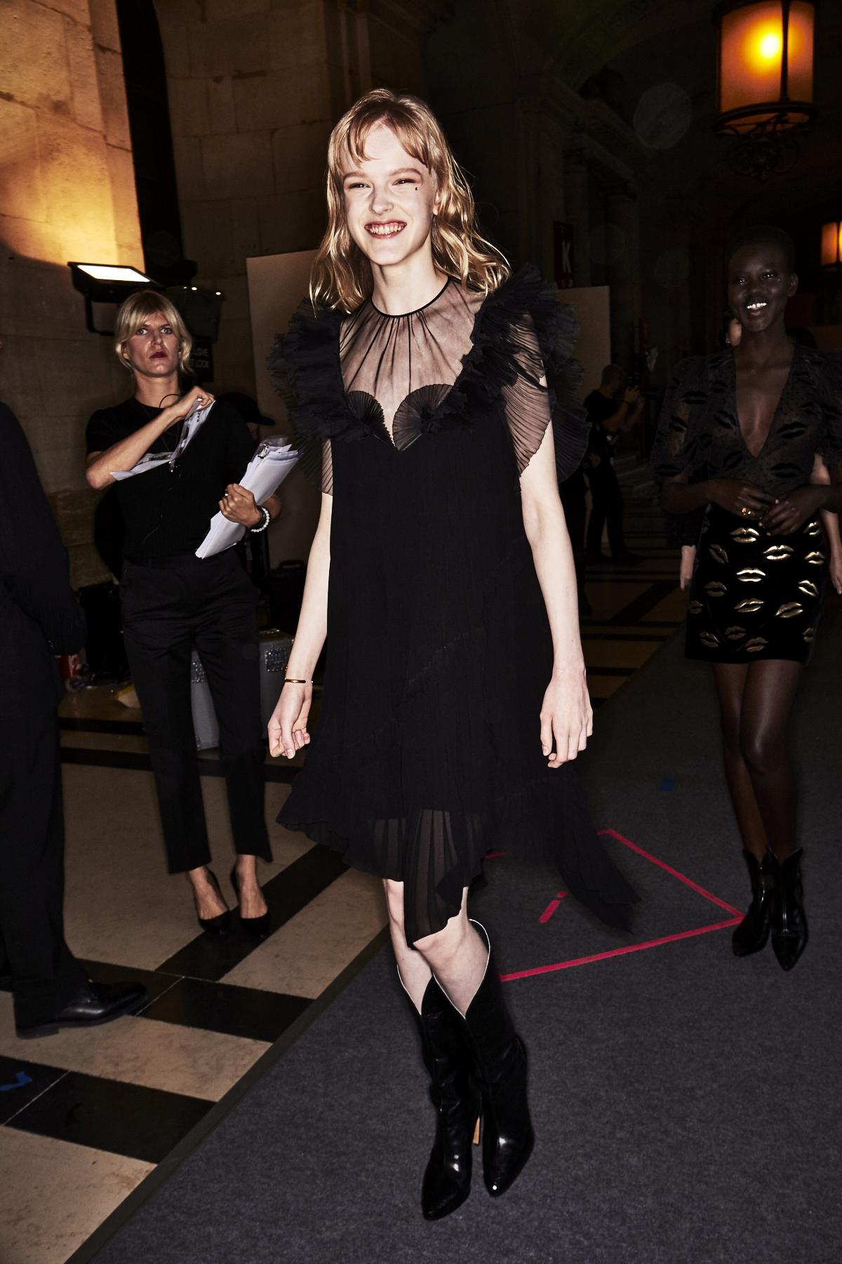 Auf dem Foto ist ein Model im Backstage-Bereich der ersten Modenschau von Designerin Claire Waight Keller für das Modehaus Givenchy in Paris zu sehen. Es handelt sich um die Präsentation der F/S 2018 Kollektion. Das Model tägt ein schwarzes Kleid mit kurzen Rüschenärmeln. Dazu kombiniert sie schwarze Cowboystiefel..