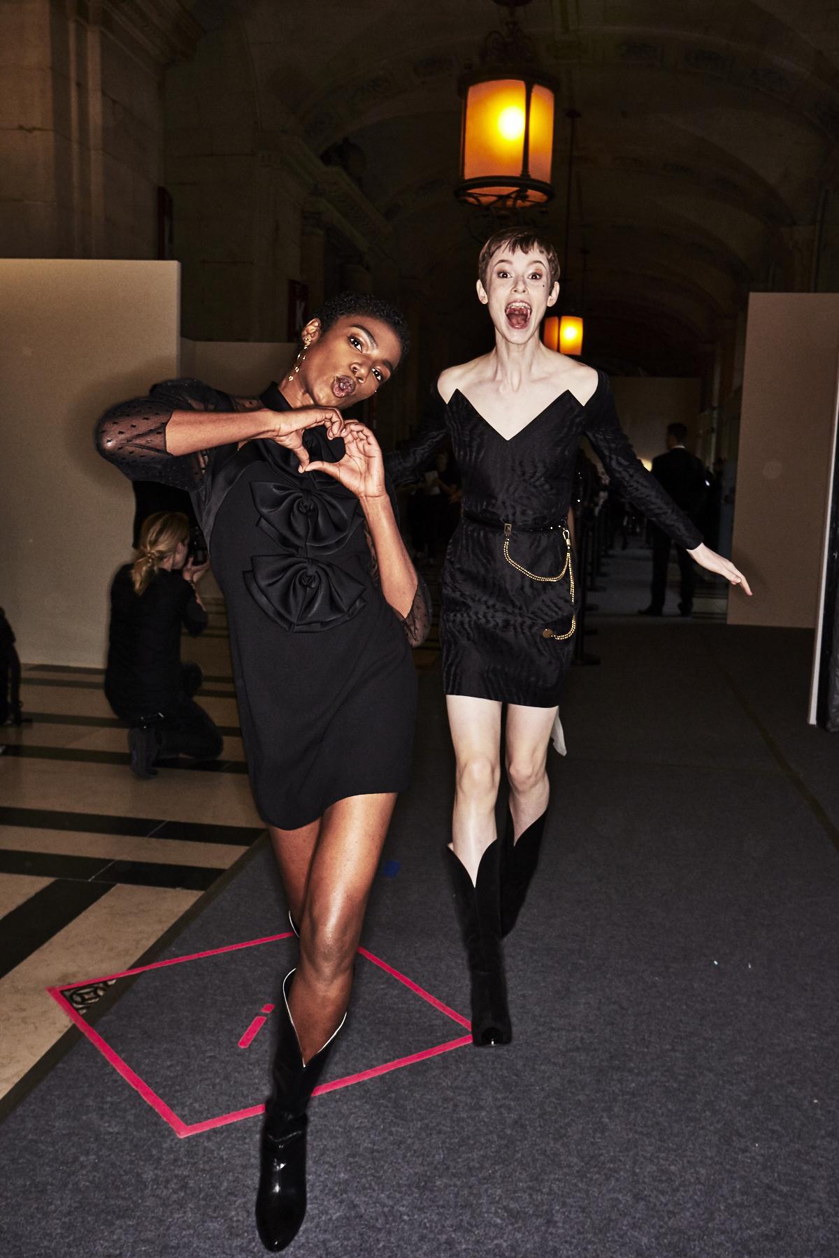 Auf dem Foto sind zwei Models im Backstage-Bereich der ersten Modenschau von Designerin Claire Waight Keller für das Modehaus Givenchy in Paris zu sehen. Es handelt sich um die Präsentation der F/S 2018 Kollektion. Beide Models tragen schwarze kurze Kleider. Dazu kombinieren sie Cowboystiefel.