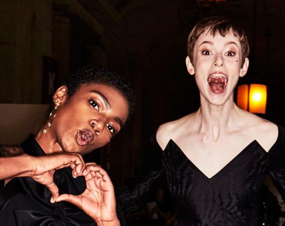 Auf dem Foto sind zwei Models im Backstage-Bereich der ersten Modenschau von Designerin Claire Weight für das Modehaus Givenchy in Paris zu sehen. Es handelt sich um die F/S 2018 Kollektion. Beide Models tragen schwarze kurze Kleider.