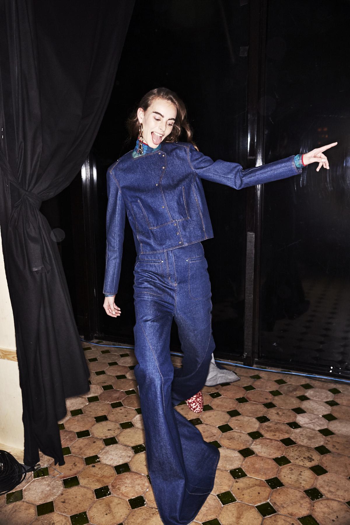 Dieses Bild zeigt ein Mädchen im Backstage Bereich der Esteban Cortazar Modenschau mit einer Jeansjacke und Jeans-Schlaghose.