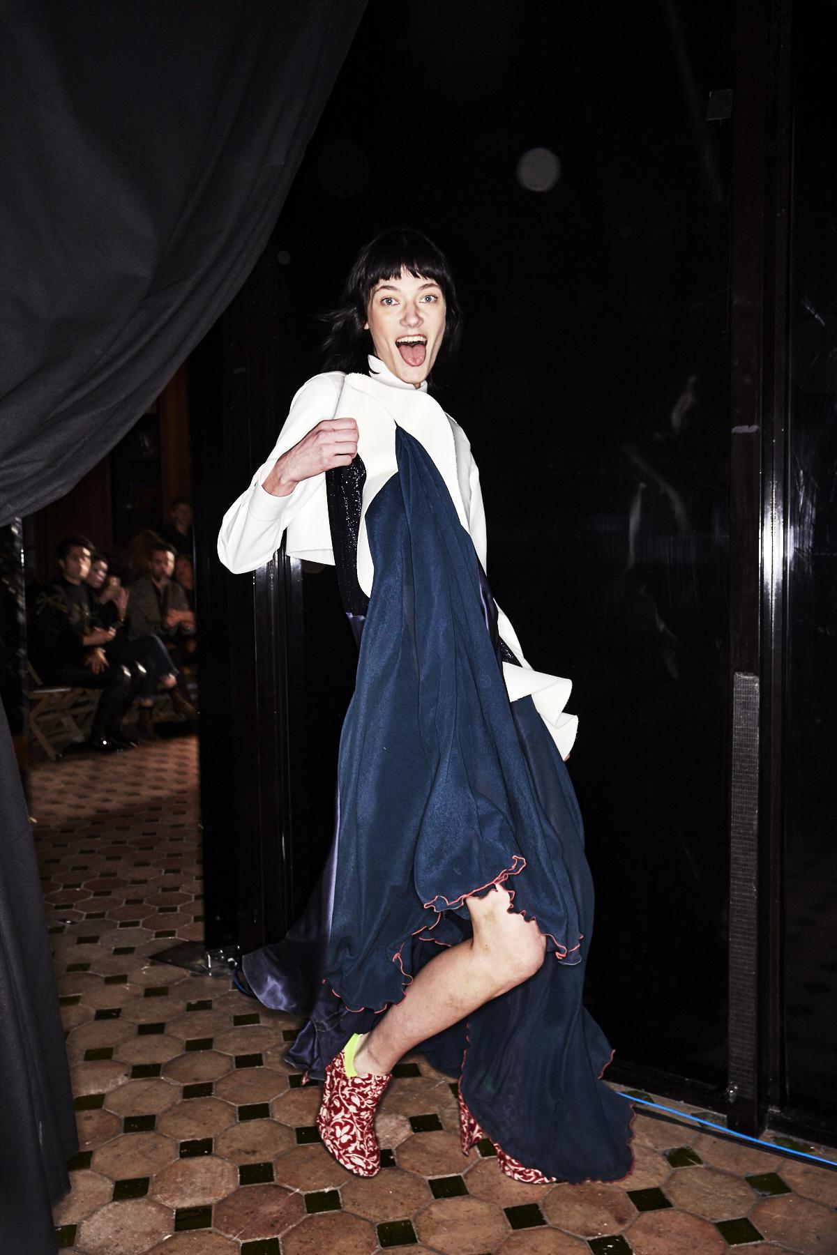 Ein Model im Backstage Bereich der Esteban Cortazar Herbst/Winter 2017 Show trägt ein langes asymmetrisches Kleid in dunklem Türkis.