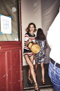 Auf dem Foto ist ein Model im Backstagebereich bei der F/S 2018 Modenschau von Sonia Rykiel zu sehen. In den Händen hält sie ein Katzenkörbchen.