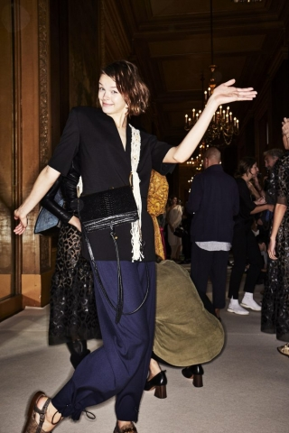 Auf dem Foto ist ein Model im Backstage Bereich bei der Frühjahr/Sommermodenschau 2018 von Designerin Stella Mc Cartney zu sehen. Sie kombiniert die Trendfarben Schwarz und Blau in Form eines halbarm Blazers und einer dunkelblauen Hose miteinander. Dazu kombiniert sie eine schwarze Crossover-Bag und einen weißen Schal.