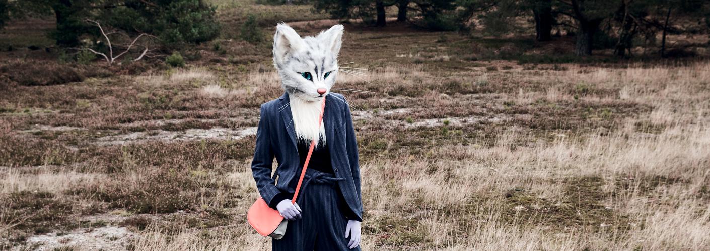 Auf den Fotos ist Katzenlady Pheline in der Fischbeker Heide bei Hamburg zu sehen. Sie trägt einen blauen Hosenanzug und kombiniert dazu einen schwarzen Pullover. Beides stammt von der Designerin Kathrin Musswessels. Außerdem trägt sie eine rot-graue Crossover-Bag von Bree und weiße Booties von Hermès.