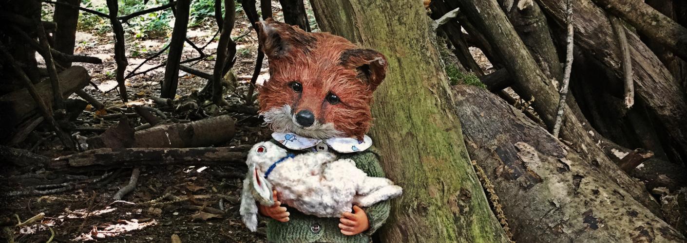 Auf dem Bild ist Fuchs als morbide Puppenfigur zu sehen. In den Händen hält er ein kleines, weißes Kaninchen. Beide Charaktere stammen von der Textilkünstlerin Annie Montgomerie.