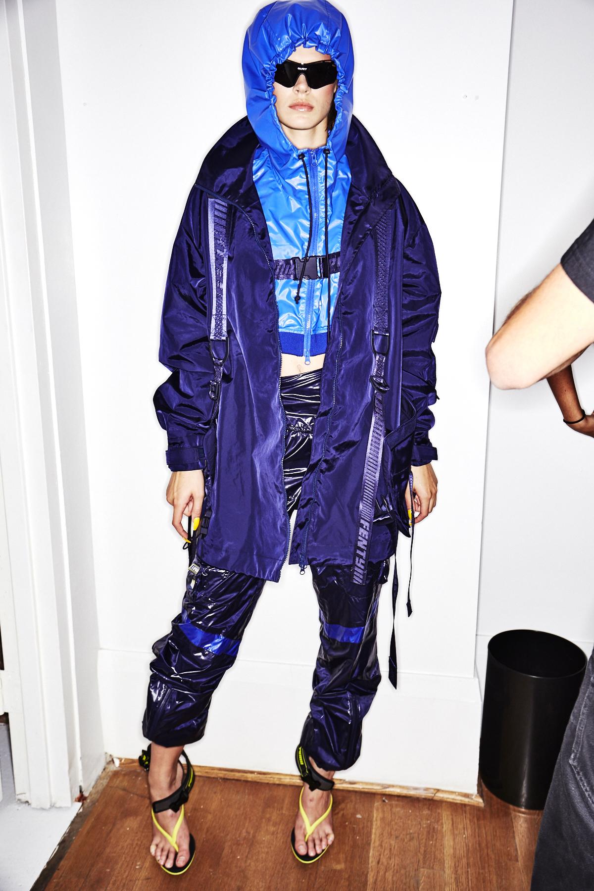 Auf dem Bild ist ein Model im Backstagebereich der Frühjahr/Sommermodenschau 2018 des Labels Pumy x Fenty by Rihanna zu sehen. Hier werden ein hellblauer Cropped-Hoodie und ein dunkelblauer Parka von einer 7/8-Sweatpants in glänzendem Nylon komplettiert. Als absolutes It-Piece wird die athletisch geformte, schwarze Sonnenbrille gehandelt.