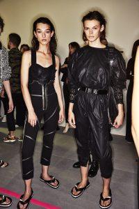 Auf dem Foto sind zwei Models im Backstagebereich der Frühjahr/Sommermodenschau von Isabel Marant zu sehen.Beide tragen schwarze Overalls, kombinieren dazu sportive Gürtel und erinnern an Catwoman.