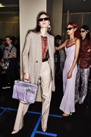 Hier sieht man ein Model im Backstage-Bereich der Acne Frühjahr/Sommer 2018 Show mit einer Hose in Plastik Optik.
