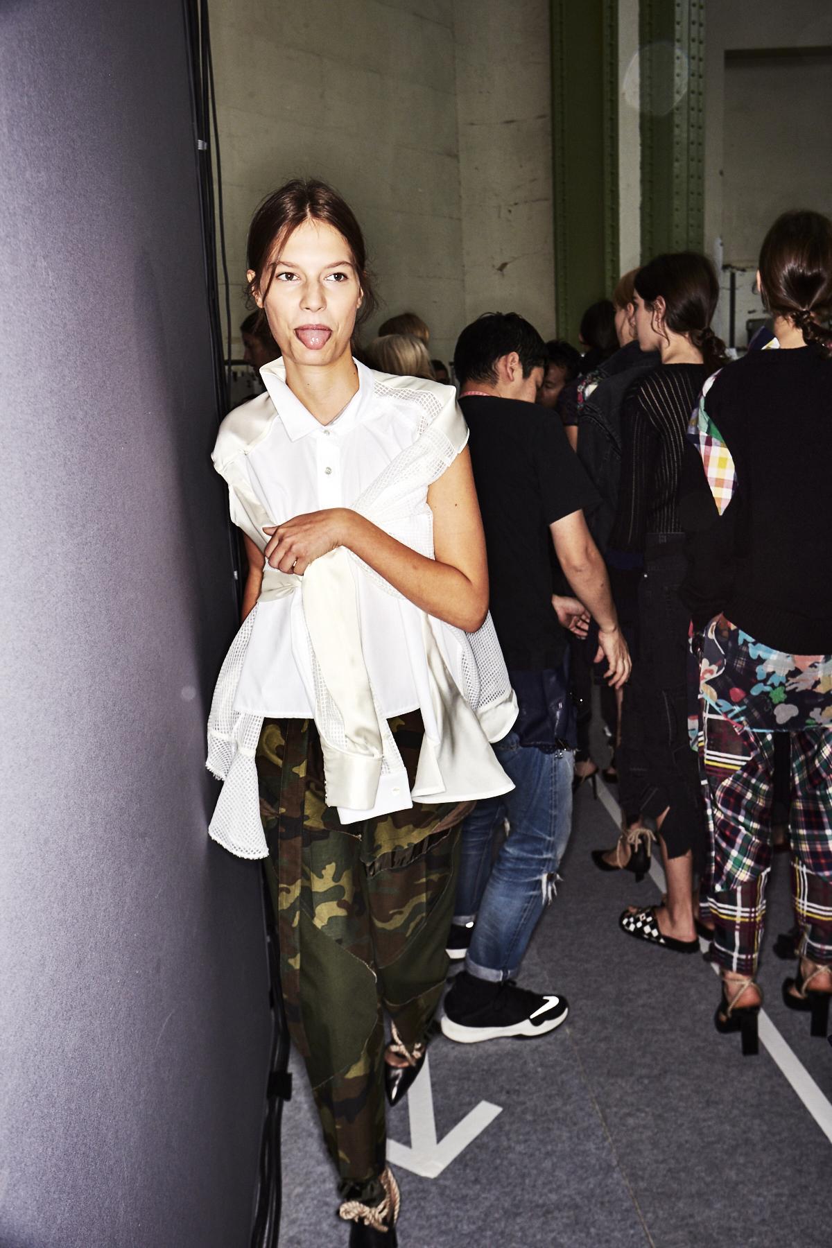 Das japanische Label Sacai stattet sein Mädchen mit einer Neuinterpretation der klassischen, weißen Button-Down-Bluse aus, deren langen Ärmel vorne an der Brust gebunden werden. Trotz der locker sitzenden Camouflage-Hose muss man sich mit diesem Outfit auf keinen Fall verstecken. Es ist Dekonstruktivismus pur.