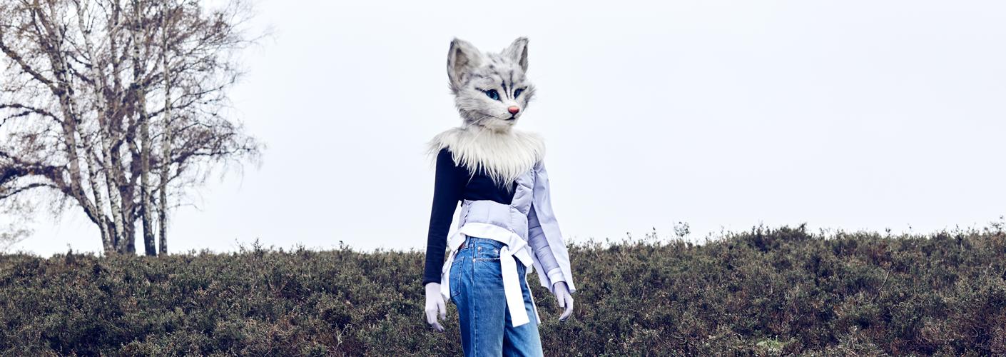 Auf dem Foto ist Katzenlady Pheline stehend in grüner Heide zu sehen. Sie trägt eine Jeans von Levi's, dazu kombiniert sie ein Longsleeve von der hanseatischen Designerin Kathrin Musswessels. Spannend wird's mit dem wattierten, halben Stepphemd von Tim Stolte, dessen gedoppelte Ärmel förmlich nach Dekonstruktivismus in Purrfection schreien! Damit sie sich die Tatzen nicht schmutzig macht, fällt ihre Wahl auf schwarz-weiße Booties vom Traditionshaus Hermès.