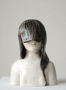 """Auf dem Bild ist eine Keramik-Torse von einem Mädchem mit überlangem Pony zu sehen. Die Skluptur hat den Titel """"Dans ma tête"""" und stammt von der Künstlerin Clémentine de Chabaneix."""