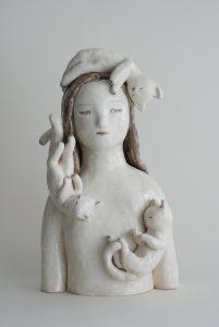 Auf dem Foto ist eine Keramik-Skulptur von der Künstlerin Clémentine de Chabaneix zu sehen. Es ist eine Torse von einem schlafenden Mädchen, das umringt ist von drei weißen schlafenden Katzen.