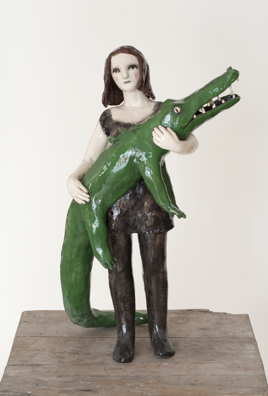 Auf dem Bild ist eine Keramik-Skulptur von der Künstlerin Clémentine de Chabaneix zu sehen. Es ist ein Mädchen, das ein grünes Krokodil im Arm hält.