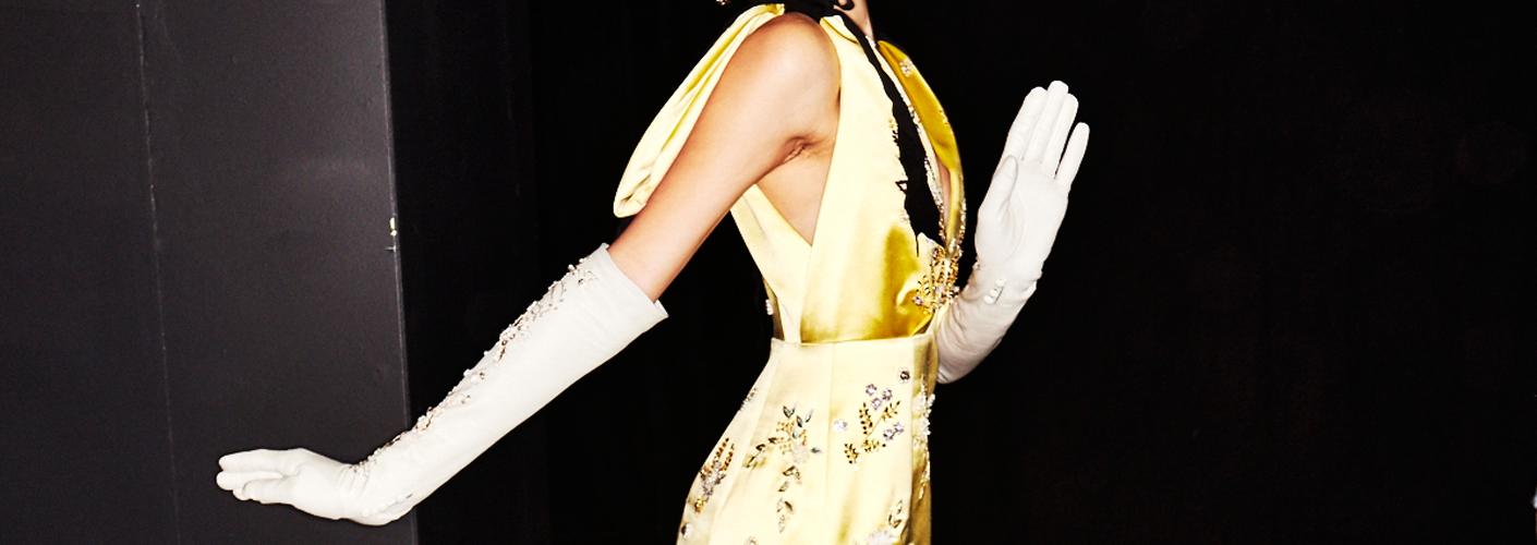 Auf dem Foto ist ein model im Backstage Bereich der Frühjahr/Sommermodenschau von Erdem zu sehen. Sie trägt ein gelbes, ärmelloses Satinkleid und kombiniert dazu weiße, lange Handschuhe.