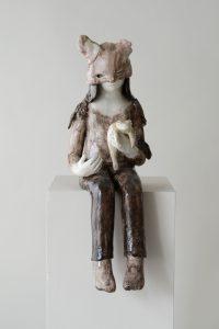 Auf dem Foto ist eine Keramik-Skulptur von der Künstlerin Clémentine de Chabaneix zu sehen. Ein Mädchen sitzt auf einem Klotz. Sie trägt eine Maske mit Katzenohren und hält eine Kröte in der Hand.