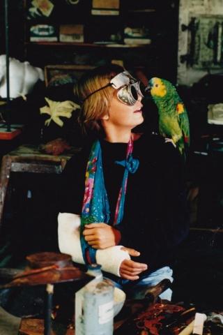 Auf dem Foto ist die Künstlerin Clémentine de Chabaneix als junges Mädchen zu sehen. Sie trägt den rechten Arm in Gips. Auf iherer linken Schulter sitzt ein grüner Papagei namens Willy.