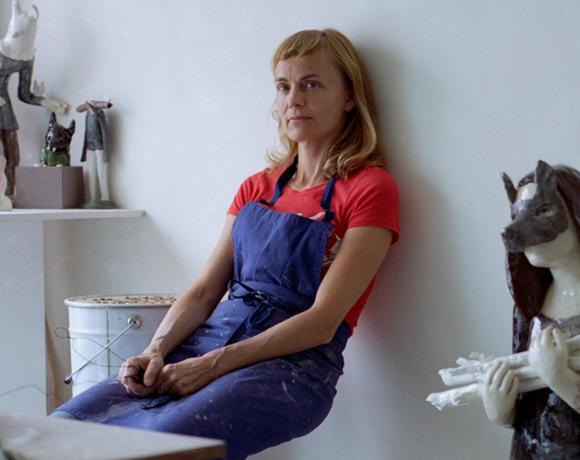 Auf dem Foto ist die französische Keramikkünstlerin Clémentine de Chabaneix in ihrem Pariser Atelier auf einem Hocker sitzend gegen die gelehnt zu sehen. Um sie herum befinden sich mehrere ihrer Keramik-Skulpturen. Das Foto stammt von Fanny Begoin.