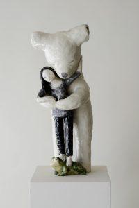 Auf dem Foto ist eine Keramik-Skulptur von der Künstlerin Clémentine de Chabaneix zu sehen. Ein Eisbär umarmt von hinten ein Mädchen, das auf einem Frosch steht. steht.