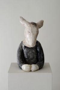Auf dem Foto ist eine Keramik-Skulptur von der Künstlerin Clémentine de Chabaneix zu sehen. Es ist eine Torse von einem Esel, der an einem Tisch sitzt.