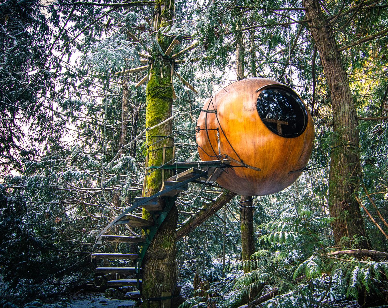 """Die magische Wunderkugel namens """"Free Spirit Spheres"""" hängt wie ein riesiges Nest zwischen den Baumwipfeln in Qualicum Bay, British Colombia in Kanada. Das Foto stammt aus dem Buch Zauberhütten und ist im Gestalten Verlag erschienen."""
