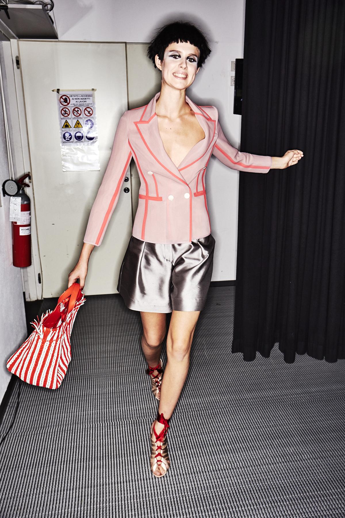 Ein Model im Backstage-Bereich der Giorgio Armani Frühjahr/Sommer 2018 Show trägt silberne Shorts zu einem Kurzjackett.