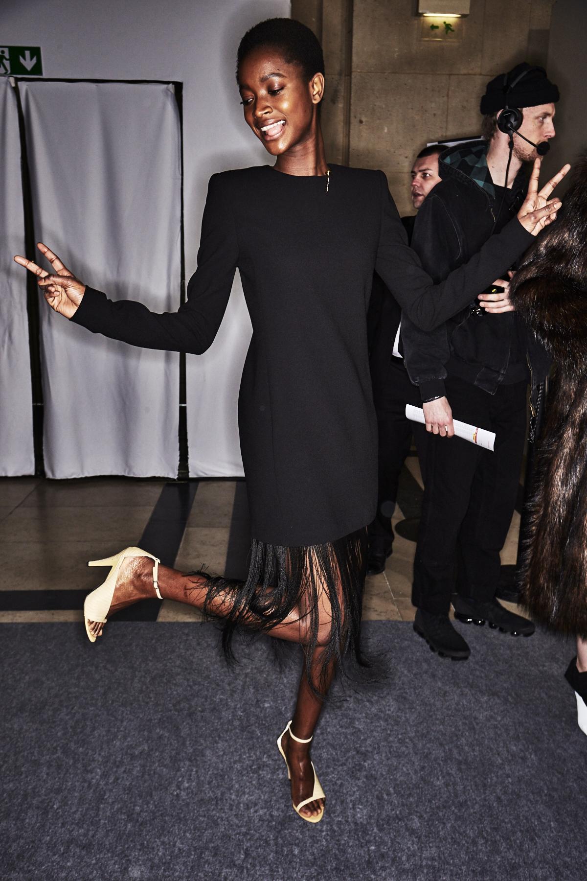 Im Backstage-Bereich der Givenchy Herbst/Winter 2018 Show trägt ein Model ein schwarzes Kleid mit langen, feinen Fransen am Saum.