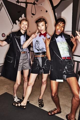 Drei Mädchen im Backstage-Bereich der Prada F/S 2018 Show tragen Shorts mit Gürteln zu Hemden und Boyfriend-Jacketts.