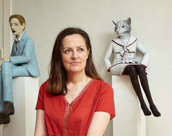 Auf dem Foto ist die Künstlerin und Bildhauerin Annette Meincke-Nagy zu sehen. Sie trägt eine rote Bluse und sitzt inmitten ihrer entstandenen Figuren und Büsten aus Pappmacheé.